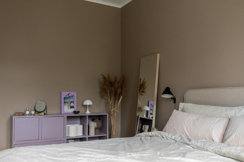 Beige Wandfarbe und Lila Sideboard im Schlafzimmer